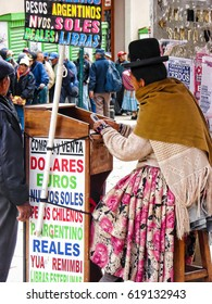 LA PAZ, BOLIVIA - APRIL,11,2015:Unidentified Bolivian woman in traditional dress works on currency exchange point on the street of La Paz