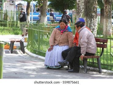 La Paz, Bolivia - December 12, 2016: Three people sit on a park bench and talk in La Paz, Bolivia on December 12, 2016