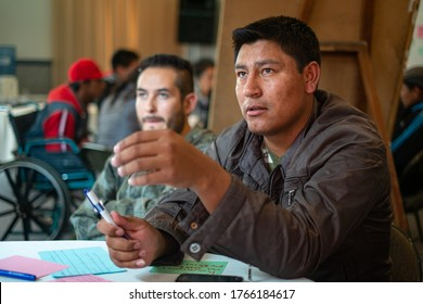 La Paz / Bolivia - December 17 2014: Young Men with Indigenous Features Sitting down Explain their Ideas to others in the Class