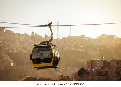 """La Paz / Bolivia - June 11 2019: Cableway transport servicie """"MI Teleférico"""" in La Paz Bolivia with constructions of the city and mountains in background at sunset"""