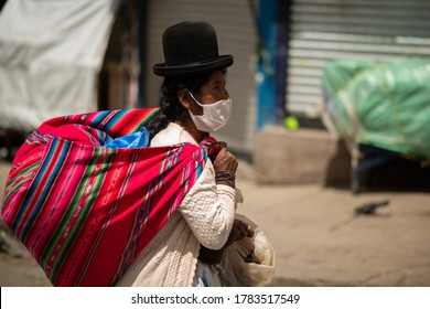 La Paz, Bolivia - Mar 26th 2020: An indigenous woman wearing a mask walks over the main market of La Paz. During the lockdown people were allowed to go once per week to buy groceries.