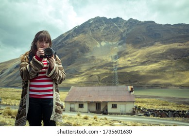 La Paz / Bolivia - September 20 2014: Young Redheaded Woman in a Striped Shirt Winks and Holds a Camera, with a Background of a Small House under the Mountain in the Bolivian Altiplano