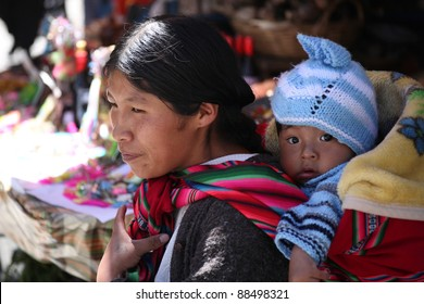 LA PAZ, BOLIVIA-JAN. 5: An unidentified Indian woman carries baby in traditional sling January 5,2009 in La Paz, Bolivia. Bolivian women use slings for centuries but now strollers compete with slings.