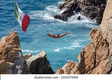 """La Quebrada, Acapulco/Mexico - December 2nd, 2018: A La Quebrada Cliff Diver courageously jumps into the sea below near a Mexican flag."