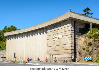 La Richardais, France - June 23, 2018: A building of the river Rance tidal power station run by french public electricity utility company EDF near Saint-Malo in Brittany with cyclists passing by.