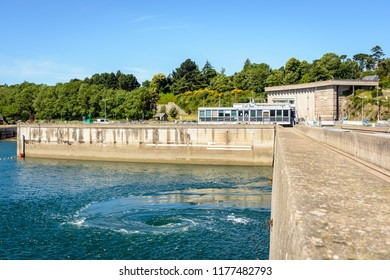 La Richardais, France - June 23, 2018: The turbines of the river Rance tidal power station, run by french public electricity utility company EDF, generate whirlpools at the surface of the water.