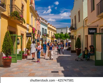 LA ROCA VILLAGE, BARCELONA, CATALONIA, SPAIN - MAY 2016: People shopping mall road of La Roca Village on a sunny day with blue sky