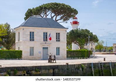 La Rochelle, France - May 07, 2019: Old port office or Bureau du Port and lighthouse in historical harbor of La Rochelle, France