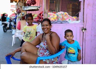 LA ROMANA, DOMINICAN REPUBLIC - 02 DECEMBER 2017: Laughing woman selling vegetables and fruits with her children which arrived in the La Romana city from the neighbouring village