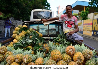 LA ROMANA, DOMINICAN REPUBLIC - 02 DECEMBER 2017: Young smiling seller of pineapple which arrived in the La Romana city from the neighbouring village