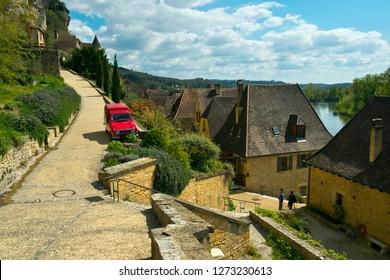 La Roque-Gageac, France -  3rd April 2017: Picturesque honeypot village of La Roque-Gageac is built under the cliffs beside the Dordogne River in Dordogne, Nouvelle Aquitaine, France.