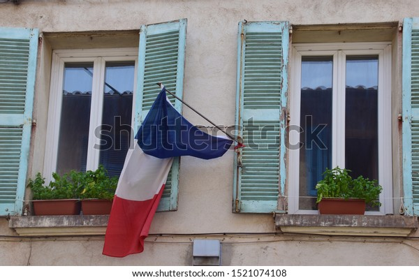 La Seyne-sur-Mer, France - July 22, 2018: Old residential building in La Seyne-sur-Mer, Provence, France. French national Flag tricolore hanging from an old residential building, Provence, France