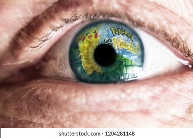 La Spezia, Italy - 10-16-2018: Pokemon let's go Pikachu game logo reflection on eye. Game addiction.