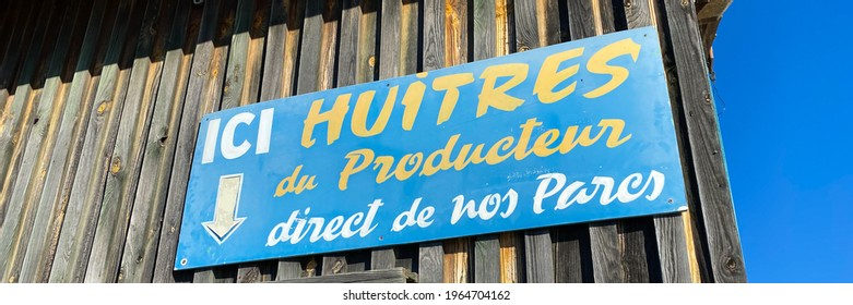 """La Teste de Buch, France - August 2020 : Sign indicating """"Here oysters from producer, direct from our parks"""" in French on the port of La Teste de Buch on the Arcachon bay"""