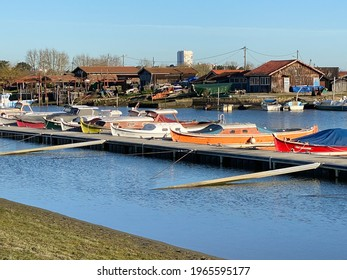 La Teste de Buch, France - August 2019 : View of the oyster farming port of La Teste de Buch with several pinasses traditional boats moored to a pontoon in the Arcachon Bay, France