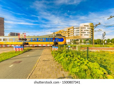 Laan der Continenten, Alphen aan den Rijn, Zuid Holland, The Netherlands, August 23, 2019:  Railway crossing Dutch Railways and passing train, closed barriers and building complex Da Vinci