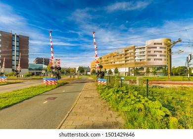 Laan der Continenten, Alphen aan den Rijn, Zuid Holland, The Netherlands, August 23, 2019: Railway crossing Dutch Railways with barriers in background building complex Da Vinci