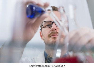 Lab man pouring fluids
