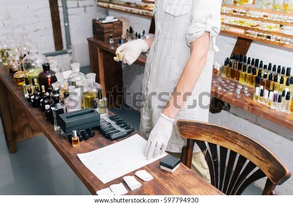 Laboratorium für Laboratorien, Nahaufnahme von Händen in sterilen Handschuhen mit einer Pipette. Nahaufnahme gelber Flaschen auf dem Regal im alten Parfüm-Labor. Flaschen und Geruchsbeispiele im Parfümshop.