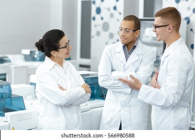 Lab team. Multiethnic group of laboratory scientists discussing their research at the lab teamwork technician specialist profession job colleagues medicine chemists biologists team study communication