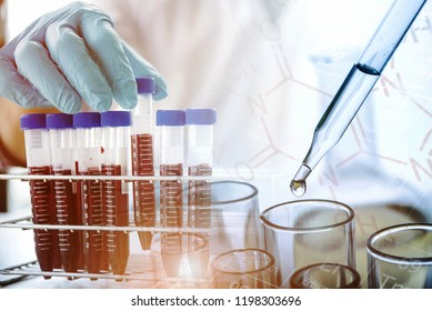 lab technician assistant analyzing a blood sample in test tube with dropping liquid sample to test tube at laboratory. Medical, pharmaceutical and scientific research and development concept.