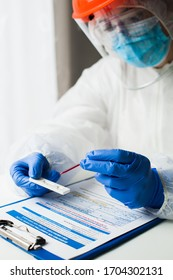 Lab technician medical scientist performing Coronavirus COVID-19 rapid diagnostic testing for antibodies, wearing personal protective equipment PPE, placing blood sample specimen on test using pipette