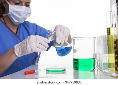 lab technician in scrubs and mask and gloves holding a test tube and beaker shot front on at a desk on a white background landscape