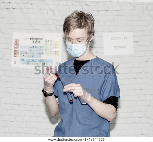 Lab technician working with a syringe and test tube wearing gloves and a face mask.
