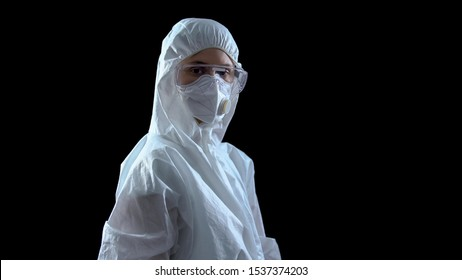 Lab worker in protective suit and mask looking at camera against dark background