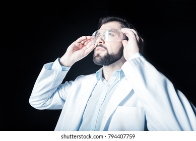 Lab worker. Smart nice bearded man standing against black background and looking up while fixing his safety glasses