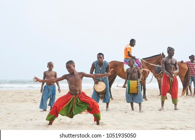 Labadi Beach, Accra, Ghana - Feb 26, 2017: Group of children and young boys dance, play traditional drums and do circus acrobatics on the beach in Accra. They wear colorful traditional dresses.