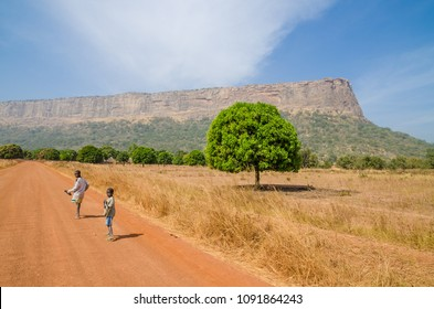 Labe, Guinea - December 20, 2013: Two unidentified boys walking on dirt road looking back with tree and mountain