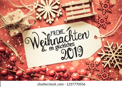 Label With German Calligraphy Frohe Weihnachten Und Ein Glueckliches 2019 Means Merry Christmas And A Happy 2019. Flat Lay With Bright Red Christmas Decoration Like Gift, Sledge And Snowflakes