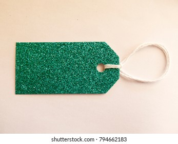 The label for the gift of sparkling green material with a rope on white background view