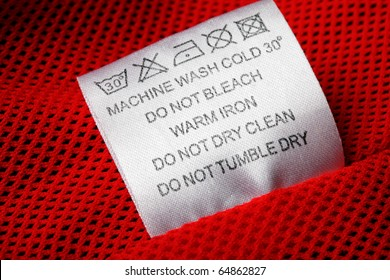 Label with laundry care symbols close-up on a red background.