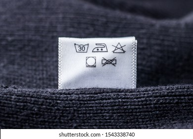 Label on clothes, black knitted sweater. Delicate care.
