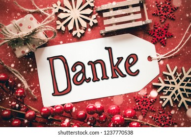 Label With Red German Calligraphy Danke Means Thank You. Flat Lay With Red Christmas Decoration Like Gift, Sledge And Snowflakes