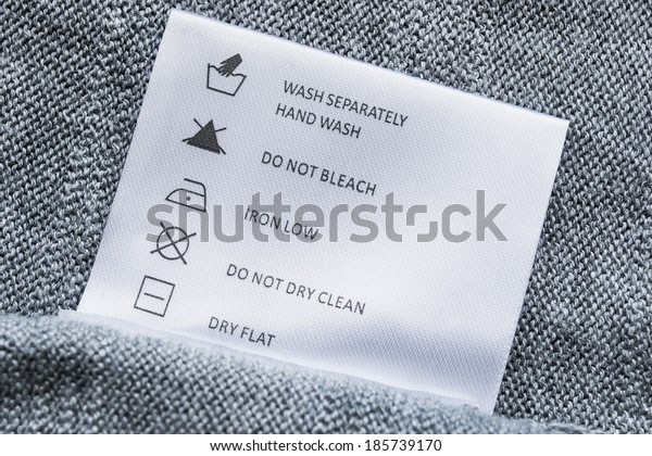 Label with washing instructions on gray knitted fabric