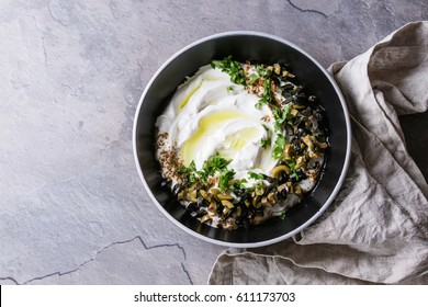 labneh middle eastern lebanese cream cheese dip with olive oil, salt, herbs, olives tapenade served in black bowl with textile napkin over gray texture metal background. Top view with space