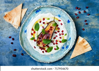 Labneh middle eastern lebanese cream cheese dip with roasted aubergine, pomegranate, mint and pita. Top view, overhead