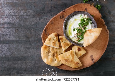 labneh middle eastern lebanese cream cheese dip with olive oil, salt, herbs served with traditional pita bread on terracotta plate over dark texture metal background. Top view with space