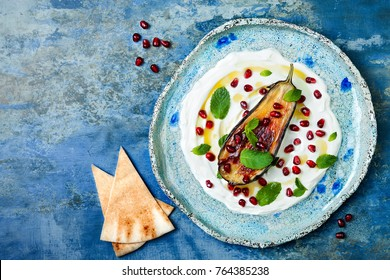 Labneh middle eastern lebanese cream cheese dip with roasted aubergine, pomegranate, mint and pita. Top view, overhead, copy space