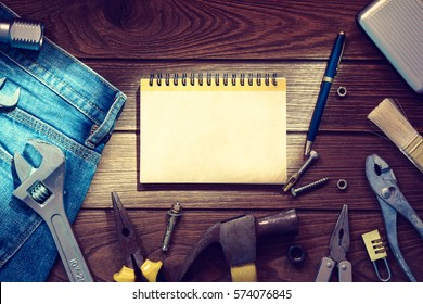 Labor day background concept - Jeans, many handy tools, blank space notebook on wooden background top view with copy space for text