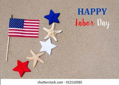 Labor Day background with flag and white, blue and red stars and starfishes on the sandy beach - USA holidays concept