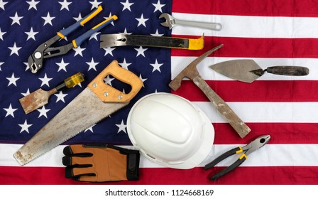 Labor Day holiday background with cloth USA flag and various worker tools