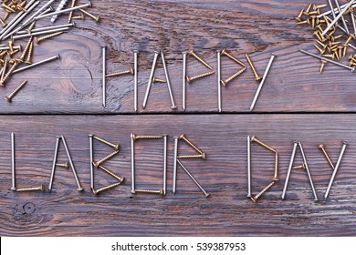Labor Day words by screws. Iron nails on wooden surface. Congratulation for a real man.