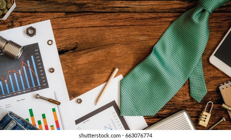 labor and fathers day background concept, financial charts and graphs, smartphone, necktie on the table, top view with copy space for your text