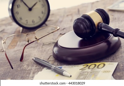 Labor law concept, gavel, clock and money on wooden table