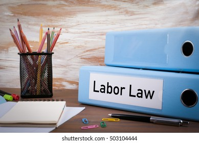 Labor Law, Office Binder on Wooden Desk. On the table colored pencils, pen, notebook paper