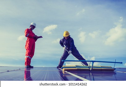 labor working on cleaning solar panel at solar power plant